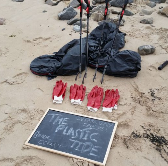 """4 pairs of red gloves on a beach, with litter collectors and plastic bags. There is a small chalkboard with the words """"The Plastic Tide"""" written on it"""