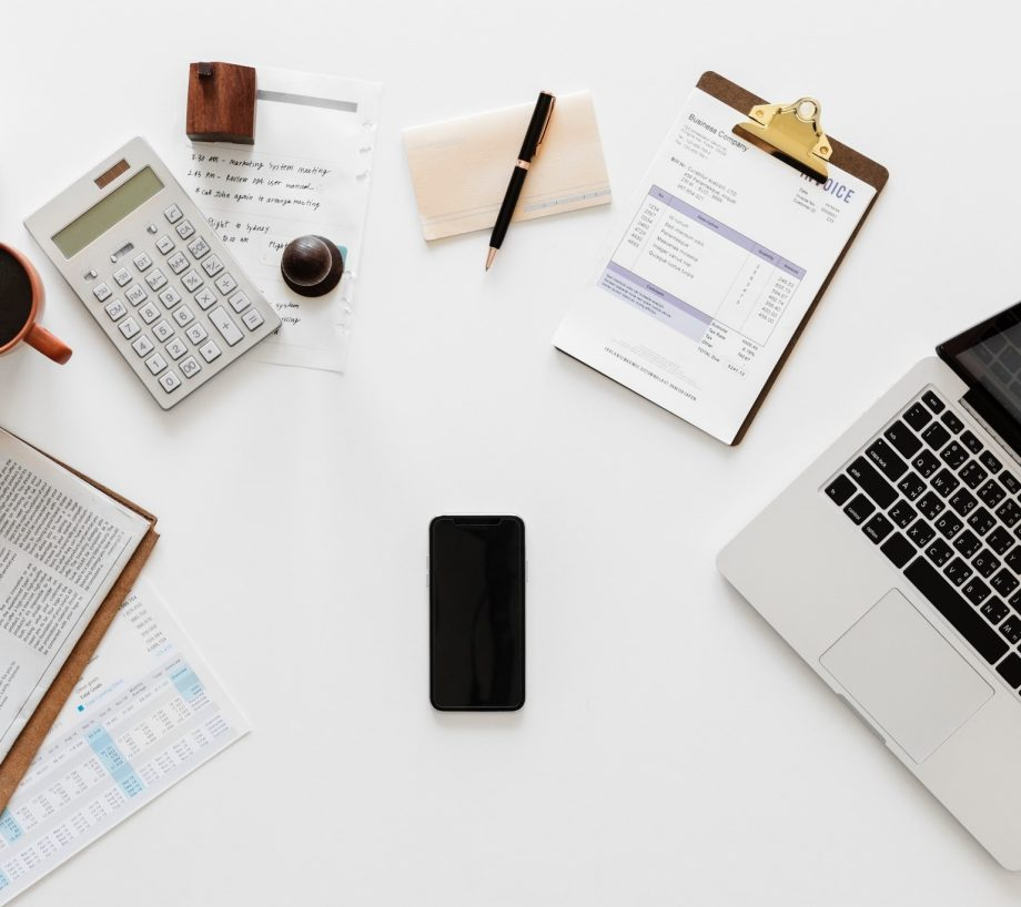 White desk with calculator, mug, laptop, notepad, pen and clipboard scattered around a smartphone