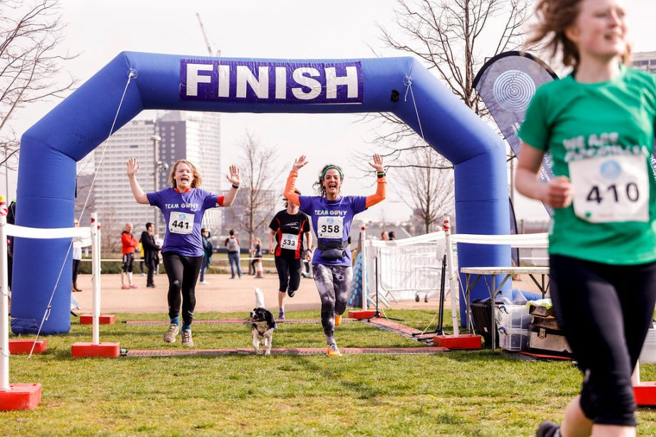Two runners and a dog crossing the finish line at a race