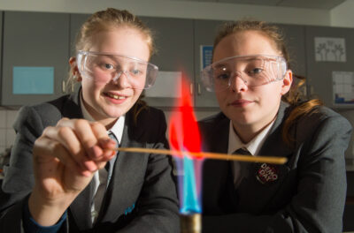 A photo of two high school students wearing safety goggles holding a thin strip of wood over the flame of a Bunsen burner.
